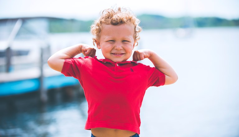 Cute toddler in red t-shirt making a strong arm pose