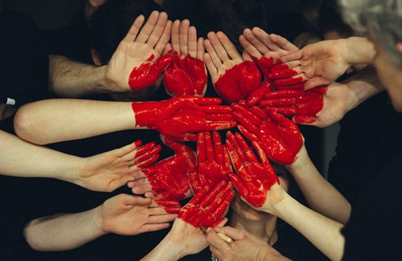 Lots of hands held together and painted red to form a heart shape