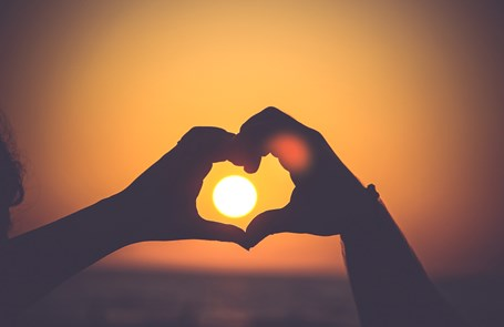 Two hands form a silhouette heart in front of a setting sun