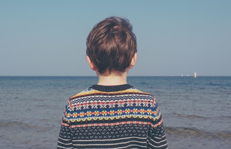 A boy stands looking out towards the sea