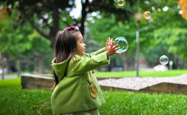 Young girl chases bubbles in a park