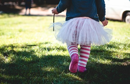 Toddler in a ballet tutu marches across grass