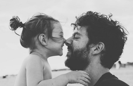 Black & white image of father and daughter rubbing noses