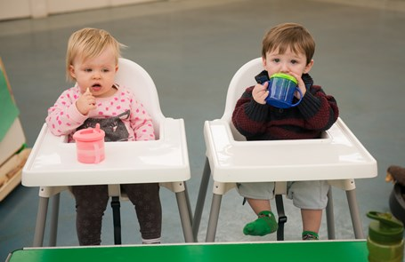 Two toddlers having a drink in their high chairs.