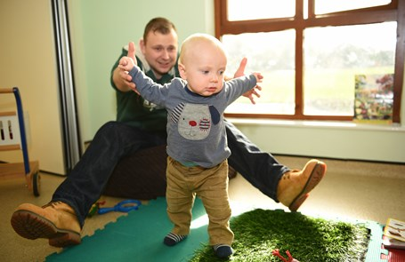 Dad helping small toddler to walk